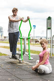Man exercising on elliptical trainer and woman. Stock Image
