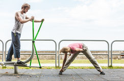 Man exercising on elliptical trainer and woman. Royalty Free Stock Image