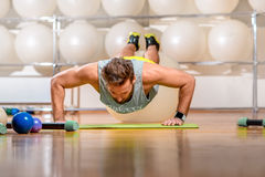 Man exercising with fitball. Sports man making push-ups with fitball in the fitness room Royalty Free Stock Photos