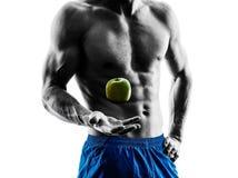 Man exercising fitness exercises eating apple Stock Image
