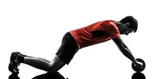 Man exercising fitness workout abdominal toning wheel silhouette. One man exercising fitness workout abdominal toning wheel in silhouette on white background stock photo