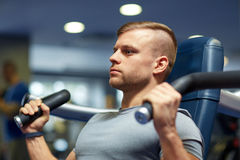 Man exercising and flexing muscles on gym machine Stock Photos
