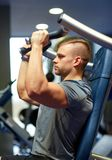 Man exercising and flexing muscles on gym machine Stock Images