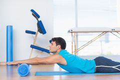 Man exercising with foam roller Stock Images