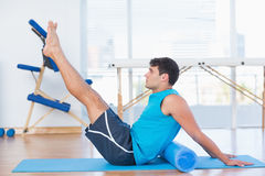 Man exercising with foam roller. In fitness studio Royalty Free Stock Photo