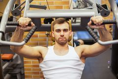 Man exercising at gym. Fitness athlete doing chest exercises on vertical bench press machine.  Royalty Free Stock Images