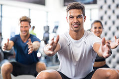 Man exercising in gym. Group of happy people exercising in squat position. Latin men doing stretching exercise and looking at camera. Portrait of smiling Stock Photography