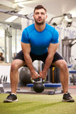 Man exercising in a gym with a kettlebell weight, vertical shot Royalty Free Stock Photos