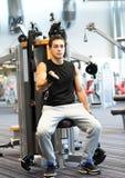Man exercising on gym machine Stock Photo