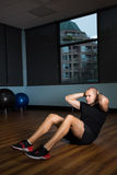 Man exercising on hardwood floor at gym Stock Images