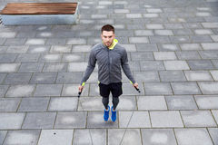 Man exercising with jump-rope outdoors. Fitness, sport, people, exercising and lifestyle concept - man skipping with jump rope outdoors royalty free stock images