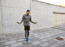 Man exercising with jump-rope outdoors. Fitness, sport, people, exercising and lifestyle concept - man skipping with jump rope outdoors Royalty Free Stock Image