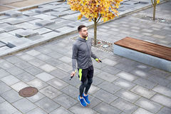 Man exercising with jump-rope outdoors. Fitness, sport, people, exercising and lifestyle concept - man skipping with jump rope outdoors royalty free stock photography