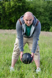 Man exercising with 3 kilos medicine ball outdoors. He is doing sport stock photos