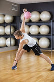 Man Exercising While Lifting Kettlebell On Hardwood Floor At Gym Stock Photos