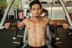 Man is exercising with machine bench press Stock Photos