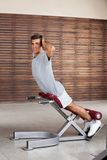 Man Exercising On Machine In Health Club Stock Photo