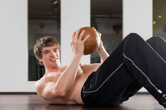 Man is exercising with medicine ball in gym Stock Image