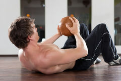 Man is exercising with medicine ball in gym Royalty Free Stock Photography