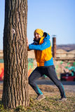Man exercising next to the tree Stock Photography