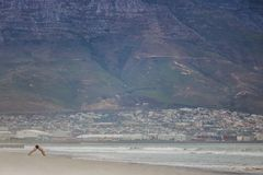 Man exercising on Paarden Eiland beach at sunrise with Table Mountain and Cape Town City in the background. Royalty Free Stock Image