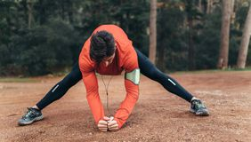 Man exercising in a park listening to music. Runner doing stretching exercises in a park listening to music. Man wearing earphones warming up before a run Stock Images