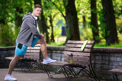 Man exercising at the park. A photo of young, handsome man exercising on the bench at the park Royalty Free Stock Image