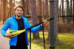 A man exercising in a park with trx fitness strips. Attractive positive male in a blue raincoat exercising in a park with trx fitness strips Royalty Free Stock Photos