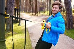 A man exercising in a park with trx fitness strips. Attractive positive male in a blue raincoat exercising in a park with trx fitness strips Stock Image