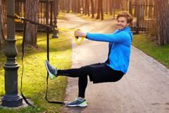 A man exercising in a park with trx fitness strips. Attractive positive male in a blue raincoat exercising in a park with trx fitness strips Stock Photo