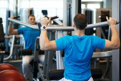 Man exercising on a simulator for dorsi. In the gym Royalty Free Stock Images
