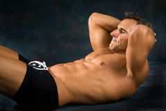 Man Exercising Situps. Athletic man performs situp calisthenics for abdominal strengthening Royalty Free Stock Images
