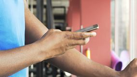 Man exercising on stationary bike at slow pace, using mobile phone, application. Stock footage stock footage