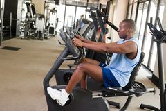 Man Exercising On Stationary Cycle. Man working out on a stationary cycle machine in a fitness club Stock Photo