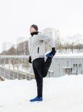 Man exercising and stretching leg on winter bridge Royalty Free Stock Image