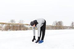Man exercising and stretching leg on winter bridge Stock Photo