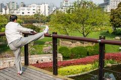 Man exercising stretching splits gucheng park shanghai china Stock Image