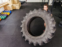 Man exercising with a tractor tire at gym. Photo of an attractive young man working out with a tractor tire at a gym Stock Photo