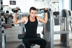 Man exercising in trainer for dorsi muscles. In the gym Stock Images