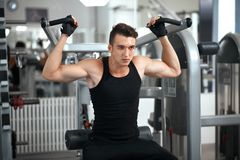Man exercising in trainer for dorsi muscles. In the gym Royalty Free Stock Photo