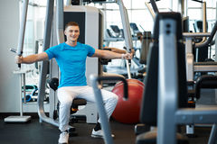 Man exercising in trainer for pectoral muscles Stock Photography