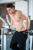 Man exercising in trainer for pectoral muscles Stock Image