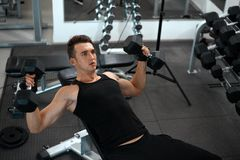Man exercising in trainer for pectoral muscles Stock Photo