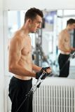 Man exercising in trainer for triceps muscles Royalty Free Stock Photo