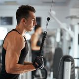 Man exercising in trainer for triceps muscles. In the gym Stock Images