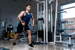 Man is exercising on a training machine in the gym. Athletic man in a T-shirt standing training on a exercise machine in the gym Stock Photos