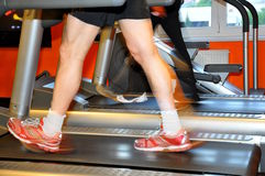 Man exercising on treadmill. Man working out on a treadmill in a fitness center. His feet are blurred from the walking motion Royalty Free Stock Image