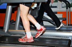 Man exercising on treadmill. Man working out on a treadmill in a fitness center. His feet are blurred from the walking motion Royalty Free Stock Photos