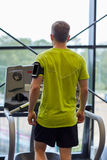 Man exercising on treadmill in gym from back Stock Images