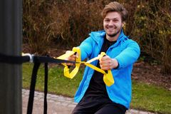A man exercising with trx fitness strips. Attractive positive male exercising with trx fitness strips Stock Images